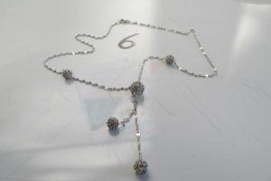 1 Collier en or gris maille fantaisie rehaussé de 5 boules ornées de pierres blanches (L42 cm). Pb 2,9g
