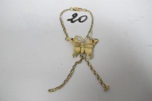 1 Bracelet de main en or brisé à décor d'un papillon orné de petites pierres bordeaux (L15cm). PB 6,5g