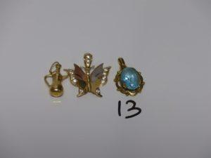 3 pendentifs en or : 1 rehaussé d'1 pierre bleue, 1 à décor d'1 cafetière, 1 à décor d'1 papillon orné de petites pierres blanches. PB 7,1grs