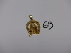 1 pendentif en or à décor d'un fer à cheval orné de petites pierres rouges et l'oeil d'un petit diamant (H3,5cm).PB 8,4g