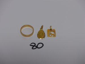 1 petit pendentif à décor d'un chien, 1 petit médaille de la Vierge et 1 alliance (td48). Le tout en or PB 5,4g