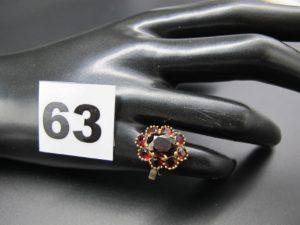 1 bague en or motif marguerite ornée de pierres couleur grenat (TD 51). PB 3,8g