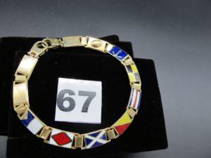 1 bracelet en or maille articulée, à decors de drapeaux emaillés (fermoir menotte) (L 21cm). PB 23,3g