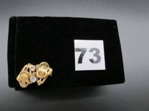1 broche en or (épingle en métal) ornée de 2 pierres blanches. PB 2,5g