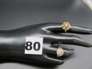 1 bague ornée d'un dome rehaussé de pierres blanches dont 1 chaton vide (TD53) et 1 bague ornée de petites pierres claires dont 3 chatons vides (TD52). Le tout en or. PB 5,8g