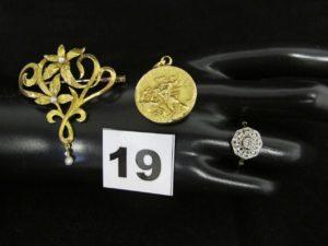 1 médaille de St Georges (diam 2,2cm), 1 broche à décor floral rehaussée de petites perles. Le tout en or PB 9,7g + 1 bague en or et platine ornée de petits diamants Taille rose (td54) PB 2,1g (total poids 11,9g)