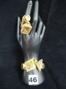 """1 bracelet marque """"Graziella"""" rigide ouvrant, à décors géometriques, orné de pierres, et 1 bague marque """"Graziella"""" à décors géometriques, ornée d'1 pierre bleutée (TD 56). Le tout en or. PB 26,9g"""