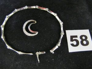 1 pendentif croissant de lune, orné d' eclats de diamants et 1 bracelet maillearticulée ornée de petits diamants (cassé, L 18cm). Le tout en or. PB 8,7g