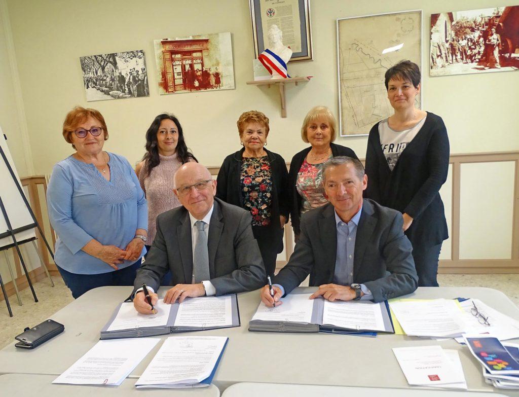 Photo de groupe. Le Maire de la commune d'Althen des paluds et le directeur du crédit municipal sont assis devant une table et signent une convention de partenariat. Derrière eux 4 femmes sont debout.