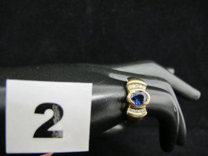 1 bague en or sertie d'une pierre ovale facetée entre 2 lignes de diamants (TD50). PB 7,2g
