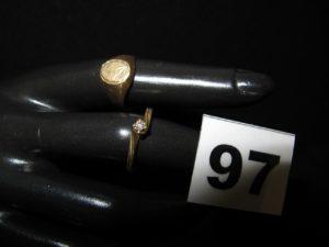 Lot de 2 bagues : 1 solitaire rehaussé d'un petit diamant (TD 53) et 1 chevalière (TD 51). Le tout en or. PB 4,5g