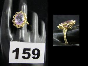 1 bague en or a monture ouvragée réhaussée d'une pierre ovale violette (L 1,4cm, TD 57). PB 5,4g