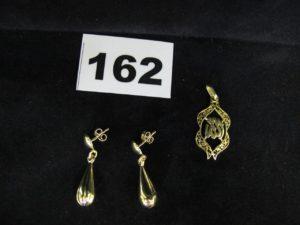 1 pendentif ouvragé d'un motif religieux (L 3,2cm)et 2 pendants d'oreille forme goutte (L2,6cm). Le tout en or. PB 5,5g