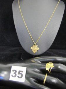 """1 alliance ciselée (TD 51, légèrement tordue), 1 pendentif motif feuille (+ qu'hier, - que demain), 1 chaîne maille forçat (L 48cm) et 1 bague """"Guyane Française"""" (TD 56). Le tout en or. PB 9,1g"""