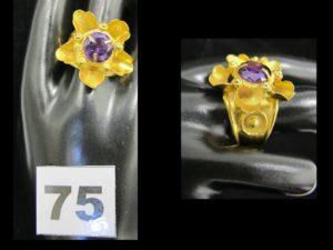 1 bague en or 916/1000 (22K) rehaussée d'une fleur volumineuse ornée en son centre d'une pierre violette (TD 59, monture tordue au dos). PB 7,2g