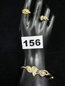 1 bague ornée de pierre blanche a motif coeur (TD 53), 1 bague ornée de pierres blanches (TD 56, 1 chaton vide) et 1 bracelet rigide ouvrant orné de pierres blanches , motif coeur (6x5,5cm). Le tout en or. PB 19,7g