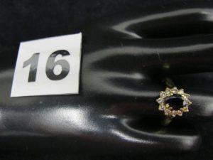 1 Bague en or forme marguerite, ornée d'une pierre bleue ovale dans un entouragede petits diamants (TD 52). PB 3,8g