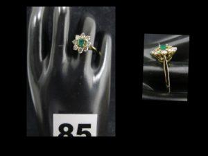1 Bague marguerite en or jaune réhaussée d'une émeraude centrale dans un entourage de 8 diamants (TL env 0,1ct chacun, TD 53). PB 3,2g
