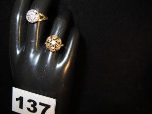 1 Bague ornée d'un dôme rehaussé de pie rres blanches (TD 53, 1 chaton vide) et 1 bague ornée de petites pierres claire s (TD 52, 3 chatons vides). Le tout en or. PB 5,8g