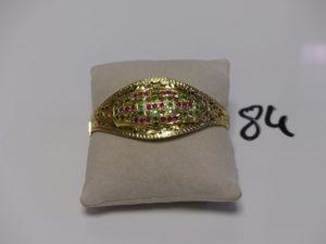 1 Bracelet rigide ouvrant en or motif central orné de pierres roses et vertes en allliage 14K. PB 13,3g