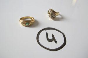 2 Bagues en or (1 ornée d'une rangée de pierres noires et blanches (td49)/1 ornée d'une pierre verte entourée de 2 pierres blanches(td53)). PB 7,30 g