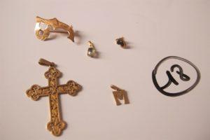 """1 Croix en or ajourée (H5cm),1 broche enor à décor d'un """"L"""", 2 pendentifs en or (1 à décor d'un """"M"""" et 1 rehaussé d'une pierre bleue),1 boucle en or rehaussée d'une pierre bleue. PB 5,7 g"""