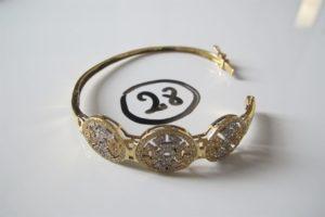 1 Bracelet 2 ors ouvrant pavé de petitespierres blanches(D 6cm). PB 13,9g