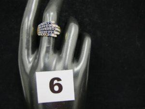 1 Bague en or réhaussée de pierres bleues et de petits diamants sur un motif en forme de main (TD 57, chatons vides). PB 3,6g