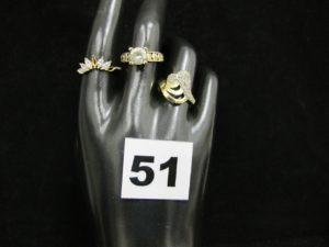 1 bague rehaussée de pierres blanches, monture décorée (TD 54), 1 bague motif couronne rehaussée de pierres (chaton vide TD 57) et 1 autre bague ornée de petites pierres blanches (TD 57). Le tout en or. PB : 7,9g