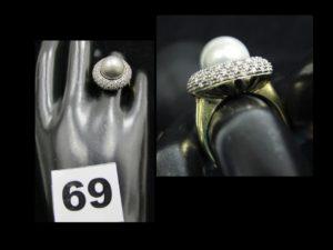 1 bague en or réhaussée d'une perle grise argentée dans un entourage bombé de petits diamants (TD 53). PB : 11,8g
