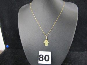 1 chaine fine maille forçat (L 41cm), 1 pendentif main de fatma décoré d'un motif étoilé. Le tout en or. PB : 1,1g