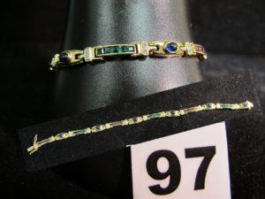 1 bracelet en or jaune serti de saphirs cabochon, entre des lignes de rubis, émeraudes, saphirs calibrés et diamants (L 18cm). PB : 14,4g