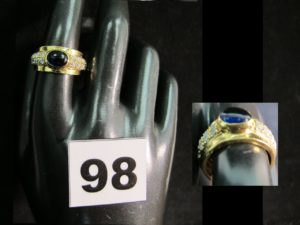 1 bague en or rehaussée d'une pierre bleue taillée en cabochon et de petites pierres blanches (TD 56). PB : 6,2g