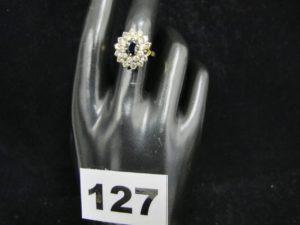 1 bague en or ornée d'une pierre bleue entourée de 2 rangées de pierres claires(1 chaton vide TD 56). PB : 5,6g