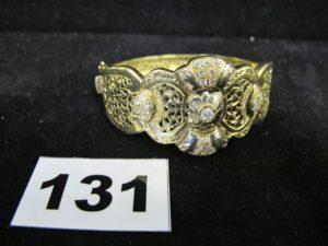 1 bracelet rigide ouvrant en or à décorsfloral ajouré ornée de petites pierres. ( 5,5 x 5cm). PB : 22,1g