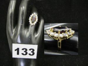 1 bague type marquise ornée d'une pierre couleur grenat dans un entourage de pierres blanches (TD 51). PB : 5,2g