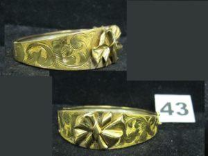 1 Bracelet en or 21K, rigide ouvrant, ciselé d'arabesques et motif noeud en relief au centre (5,7 x 5,2cm). PB 19,9g