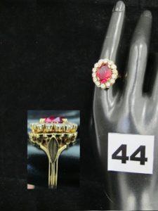 1 Bague marguerite en or, ornée d'une pierre rouge centrale dans un entourage de pierres blanches (TD 57). PB 8,1g