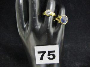 1 Bague serti clos d'une pierre violett e (TD 51) et 1 bague serti clos d'une p ierre blanche (TD 51). Le tout en or 21 K. PB 6,7g