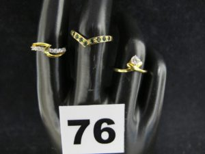 1 Bague ornée d'une pierre blanche ( TD 51), 1 ornée de petites pierres blanches ( TD 50) et une bague motif V sertie d e petites pierres vertes ( TD 53). Le tout en or. PB 5,1g
