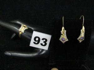 1 Bague ornée de petites blanches (chaton vide, TD 56) et 2 pendants d'oreilles ornés d'une pierre centrale violette entourée de petites pierres blanches (chatons vides). Le tout en or. PB 5,4g