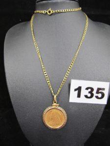 1 chaine maille gourmette ( L52 cm) et 1 pendentif contenant 1 pièce de la Reine Victoria de 1896 verouillée par un fermoir à vis. Le tout en or. PB 17,3g