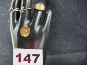 """1 bague en or gris Toi & Moi ornée de petites pierres (TD 57), 1 bague en or bicolore réhaussée d'une pierre rouge et de 2 liserets de pierres blanches (TD 56), 1 chevalière gravée """"LB"""" (TD 51) et 1 médaille ange. Le tout en or. PB 7,6g"""