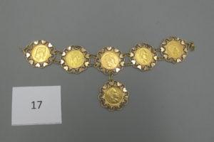 1 Bracelet en or rehaussée de 6 pièces en or 22 k de 20 frs dont 1 montée en pampille,à décor de coeurs (L21cm). PB 61g.