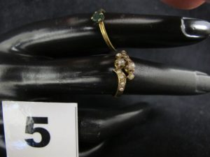 1 Bague ornée d'une emeraude elimée (TD49) et 1 bague ornée de nombreuses petites perles (TD 50). Le tout en or. PB 2,7g