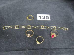 1 Bague tourbillon tordue avec une pier re blanche, 1 bague sectionnée ornée d' une pierre rouge, 1 bague tordue et sectionnée, 1 bague ajouré d'un motif floral et 1 bracelet en or ajouré (4 chatons vides)( L18cm). Le tout en or. PB 9,6g