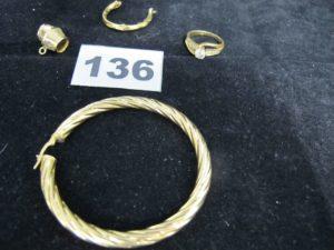 1 Pendentif tonneau, 1 bague fendue ornée de pierres ( TD 54 chatons vides), 1 creole et un debris d'or. Le tout en or. PB 12,8g