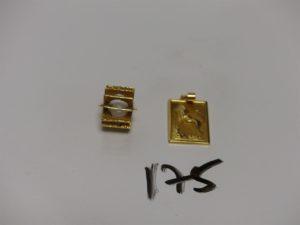 1 pendentif plaque en or signe du lion et 1 pendentif en or orné d'1 perle mobile (fragile). PB 5,8g