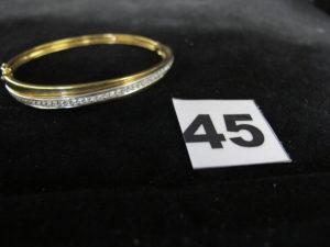 1 Bracelet bicolore rigide ouvrant en or rehaussé d'un liseré de diamant (5,5 x 5 cm). PB 18,6g