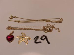 2 pendentifs en or (1 coeur ornée d'une pierre rouge)(1 etoile manque belière) et 2 chaines en or (1 cassée)(1 fine maille gourmette). PB 5,4g